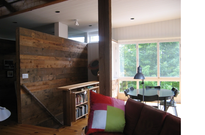 Living area, with recycled wood wall, book case, and fully openable window wall